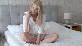 Härlig blond kvinna som dricker ett kaffe, medan sitta på hennes säng hemma arkivfilmer