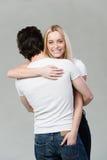 Härlig blond kvinna som ger hennes make en kram royaltyfria foton