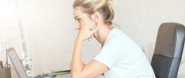 Härlig blond kvinna som hemma arbetar på bärbara datorn Henne ` s som fokuseras på arbete Frilans hemmastatt begrepp för arbete arkivbild