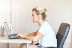 Härlig blond kvinna som hemma arbetar på bärbara datorn Henne ` s som fokuseras på arbete Frilans hemmastatt begrepp för arbete royaltyfri foto
