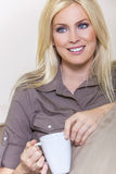 Härlig blond kvinna som hemma dricker te eller kaffe Royaltyfri Bild