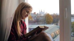 Härlig blond kvinna som hemma läser ett boksammanträde på en fönsterbräda stock video