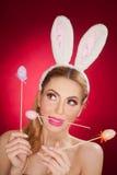 Härlig blond kvinna som påskkanin med kaninöron på röd bakgrund, studioskott Ung dam som rymmer tre kulöra ägg arkivfoto
