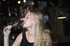 Härlig blond kvinna som tycker om ett exponeringsglas av champagne eller prosecco Royaltyfri Fotografi