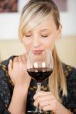 Härlig blond kvinna som tycker om ett exponeringsglas av vin Arkivbild