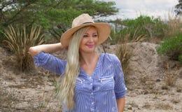 Härlig blond kvinna som utomhus bär hatten i prärien arkivbilder
