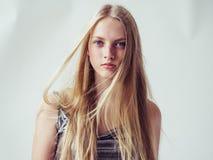 Härlig blond kvinnaflicka med slätt långt blont hår och friaren royaltyfria foton