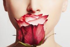 Härlig blond kvinnaframsida och blomma Flicka och ro applicera genomskinlig fernissa för omsorgshud Arkivbilder