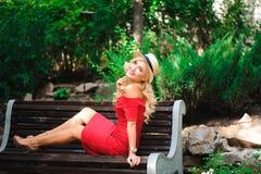 Härlig blond kvinnlig som sitter på en bänk royaltyfri bild