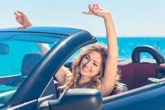 Härlig blond le ung kvinna i cabrioletöverkantbilen som ser åt sidan, medan parkerat nära havstrand arkivbilder