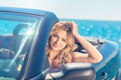 Härlig blond le ung kvinna i cabrioletöverkantbilen som ser åt sidan, medan parkerat nära havstrand arkivfoto