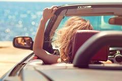 Härlig blond le ung kvinna i cabrioletöverkantbilen som ser åt sidan, medan parkerat nära havstrand royaltyfri bild