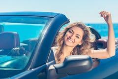 Härlig blond le ung kvinna i cabrioletöverkantbilen som ser åt sidan, medan parkerat nära havstrand royaltyfri fotografi