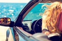 Härlig blond le ung kvinna i cabrioletöverkantbilen som ser åt sidan, medan parkerat nära havstrand arkivfoton