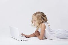 Härlig blond liten flicka med netbook, vit bakgrund Fotografering för Bildbyråer