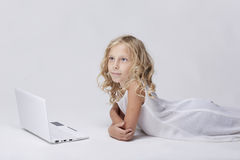 Härlig blond liten flicka med netbook, vit bakgrund Arkivfoton