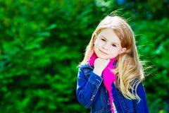 Härlig blond liten flicka som bär den rosa halsduken fotografering för bildbyråer
