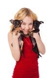 Härlig blond liten flicka som rymmer två valpar som bär röd dre Royaltyfri Foto