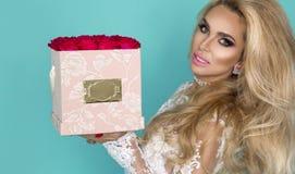 Härlig blond modell i den eleganta klänningen som rymmer en bukett av rosor, blommaask Valentin och födelsedaggåva på en blå bakg royaltyfria foton
