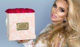 Härlig blond modell i den eleganta klänningen som rymmer en bukett av rosor, blommaask Valentin och födelsedaggåva på en blå bakg royaltyfri bild