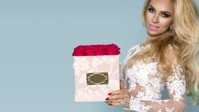 Härlig blond modell i den eleganta klänningen som rymmer en bukett av rosor, blommaask Valentin och födelsedaggåva på en blå bakg royaltyfri fotografi