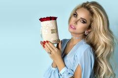 Härlig blond modell i den eleganta klänningen som rymmer en bukett av rosor, blommaask Valentin och födelsedaggåva på en blå bakg arkivfoto