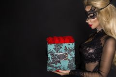 Härlig blond modell i den eleganta klänningen som rymmer en gåva, blommaask med rosor valentin för gåva s arkivfoton