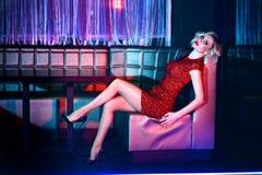 Härlig blond modell i den röda korta inpassade paljettklänningen som kopplar av på den fyrkantiga soffan i nattklubb Royaltyfri Fotografi