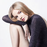 härlig blond sexig kvinna Flicka med perfekt kroppsammanträde på stol Härligt långt hår och ben, slät ren hud, hudomsorg Royaltyfria Bilder