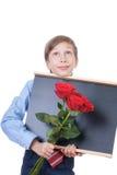 Härlig blond skolpojke som bär en skjorta och ett band som rymmer le för svart tavla och för röda rosor Royaltyfria Foton
