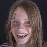 Härlig blond ung flicka med fräknar inomhus på svart bakgrund, closeupstående royaltyfri foto