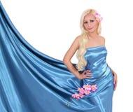 Härlig blond ung kvinna i den silk klänningen för turkos med blommor arkivbilder