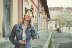 Härlig blond ung kvinna som går på gatan som talar på telefonen Royaltyfria Bilder