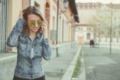 Härlig blond ung kvinna som går på gatan som talar på telefonen Royaltyfria Foton