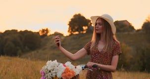Härlig blondin i en hatt med en cykel som ser mobiltelefonskärmen och en korg på styret med blommor arkivfilmer