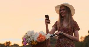 Härlig blondin i en hatt med en cykel som ser mobiltelefonskärmen och en korg på styret med blommor stock video
