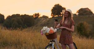 Härlig blondin i en hatt med en cykel som ser mobiltelefonskärmen och en korg på styret med blommor lager videofilmer