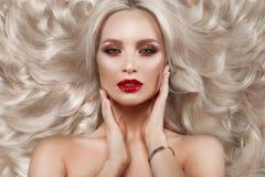 Härlig blondin i ett Hollywood sätt med krullning, naturlig makeup och röda kanter Skönhetframsida och hår royaltyfria foton