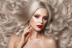 Härlig blondin i ett Hollywood sätt med krullning, naturlig makeup och röda kanter Skönhetframsida och hår royaltyfri fotografi