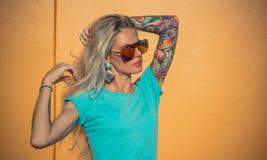 Härlig blondin i solglasögon som poserar på kameran Stående på bakgrunden av den ljusa orange väggen Modern hipster Royaltyfri Bild