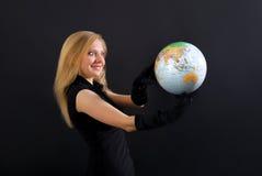 Härlig blondin i svart med jordklotet Arkivbilder