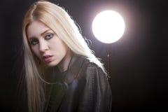 Härlig blondin med ett studioljus bakom och linssignalljuset Arkivbilder