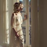 Härlig blondin på fönstret Arkivbild