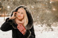 Härlig blondin som talar på telefonen i vinter arkivfoton