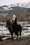 Härlig blondin Viking i en svart udde på hästrygg Royaltyfri Fotografi