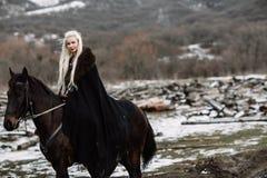 Härlig blondin Viking i en svart udde på hästrygg Arkivfoto