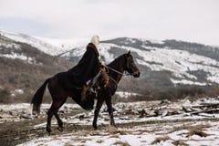 Härlig blondin Viking i en svart udde på hästrygg Royaltyfri Bild