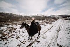 Härlig blondin Viking i en svart udde på hästrygg Arkivfoton