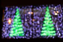 Härlig Bokeh bakgrund av två julgranar och purpurfärgade ljus royaltyfria foton