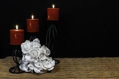 Härlig bouquie av vita rosor, röda stearinljus som sätta sig på svarta stearinljushållare på den matta för ingreppsställe och trä fotografering för bildbyråer